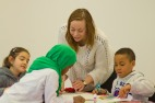 The workshop: Educator assists children with their collages