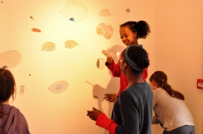 Children sticking eyes to the gallery wall